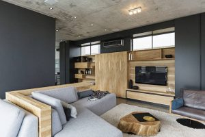 Salon en bois avec canapé gris et murs gris foncé