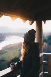 Jeune femme en train de boire son café sur le balcon de son chalet de montagne